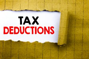 Word, writing Tax Deductions. Business concept for Finance Incoming Tax Money Deduction written on white paper on the yellow folded paper.